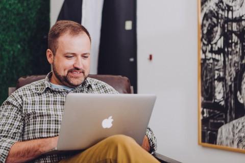 Man smiling using mac book